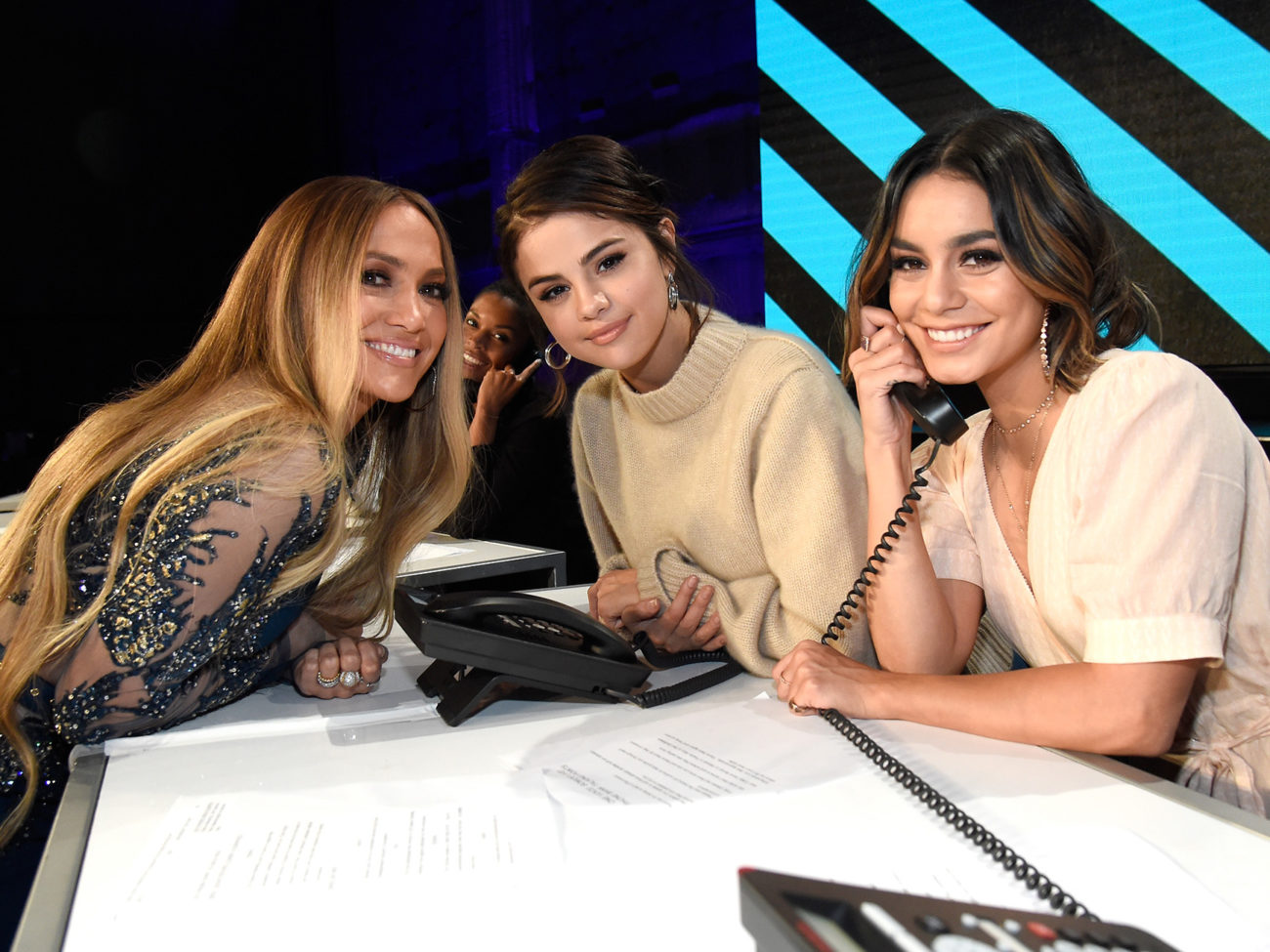"""LOS ANGELES, CA - OCTOBER 14:  In this handout photo provided by One Voice: Somos Live!, singers Jennifer Lopez and Selena Gomez and actor Vanessa Hudgens participate in the phone bank onstage during """"One Voice: Somos Live! A Concert For Disaster Relief"""" at the Universal Studios Lot on October 14, 2017 in Los Angeles, California.  (Photo by Kevin Mazur/One Voice: Somos Live!/Getty Images)"""